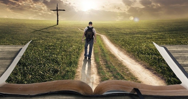 man walking on the Bible towards a cross
